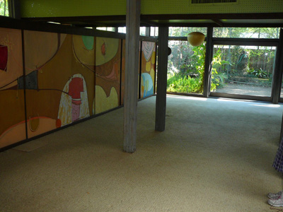 A view from den area into living area.  The large mural hides storage for media, books, display, etc.  The mural was painted in 1969 by Robert Madden.