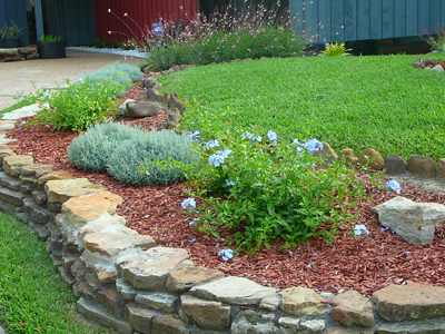 I used rocks to create a bed to highlight the retaining wall and planted perennials and topped with mulch.