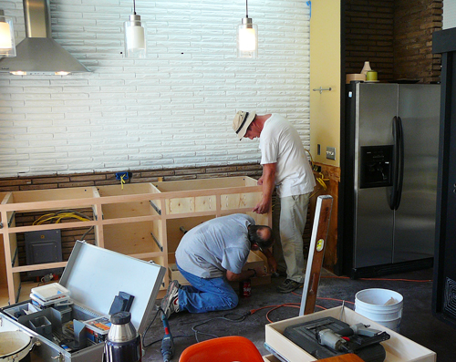 We start the renovation.  Our carpenter was AMAZING.  I feel so blessed to have found him.  Richie helps him install one side of the kitchen cabinets.